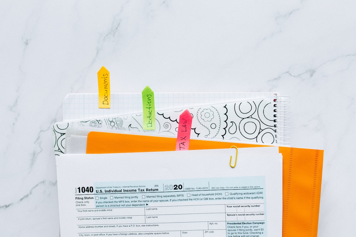 Tax forms on top of tabbed folders of tax documents